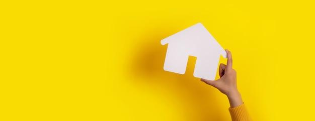 Ręka trzyma dom na żółtym tle, koncepcja inwestycji w nieruchomości, układ panoramiczny