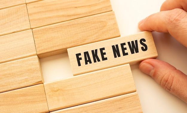 Ręka trzyma drewnianą kostkę z napisem fake news. koncepcja pozytywnego myślenia