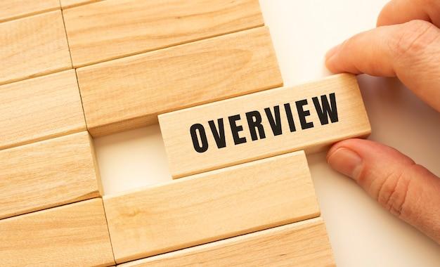 Ręka trzyma drewnianą kostkę z napisem przegląd. koncepcja pozytywnego myślenia