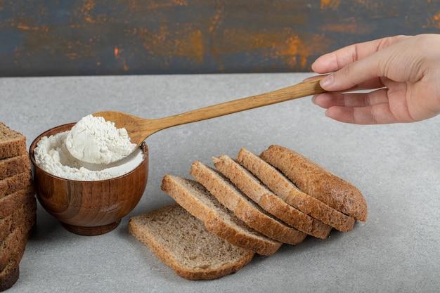 Ręka trzyma drewnianą łyżką mąki i kromki chleba.