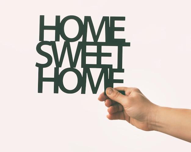 Ręka trzyma drewniane frazy home sweet home. koncepcja kupna lub budowy domu marzeń