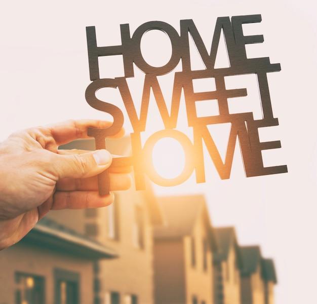 Ręka trzyma drewniane frazy home sweet home przed domem niewyraźne. koncepcja kupna lub budowy domu marzeń