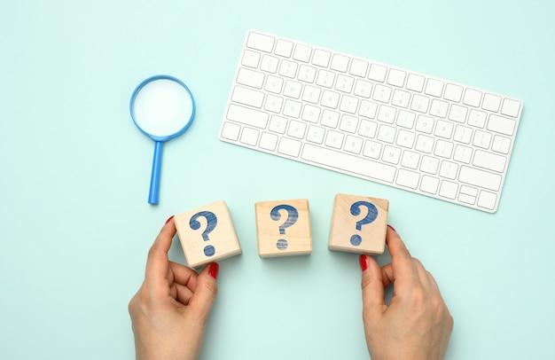 Ręka trzyma drewniane kostki z napisem. koncepcja pomocy w nawigacji strony internetowej, pytania i odpowiedzi