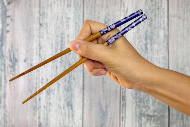Ręka trzyma drewniane pałeczki do jedzenia orientalnych potraw
