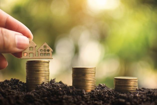 Ręka trzyma drewnianego domu modela z monetami na glebowym i drzewnym bokeh tle