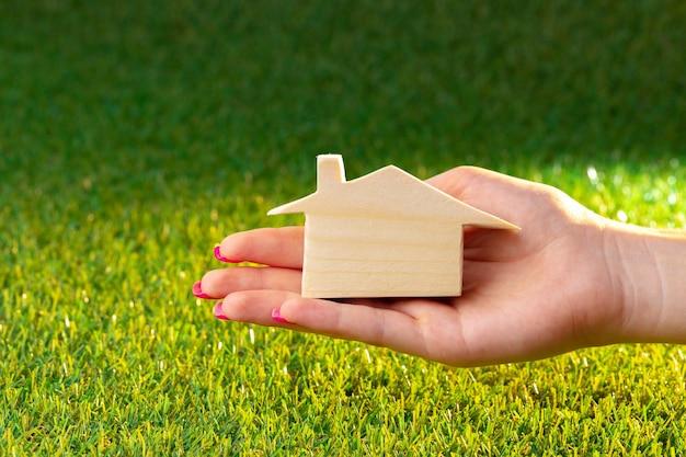 Ręka trzyma drewniany dom model nad trawą z bliska