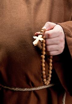 Ręka trzyma drewniany różaniec