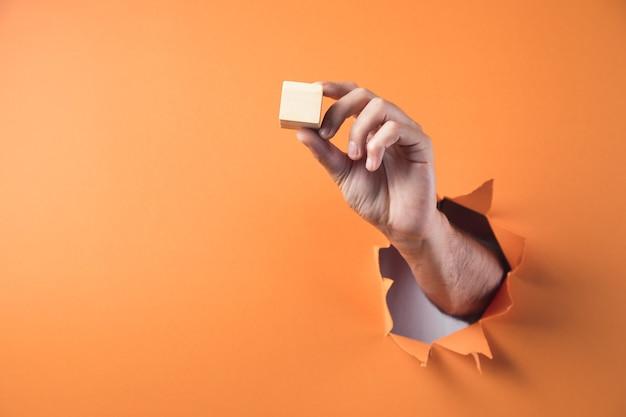 Ręka trzyma drewniany sześcian na pomarańczowym tle