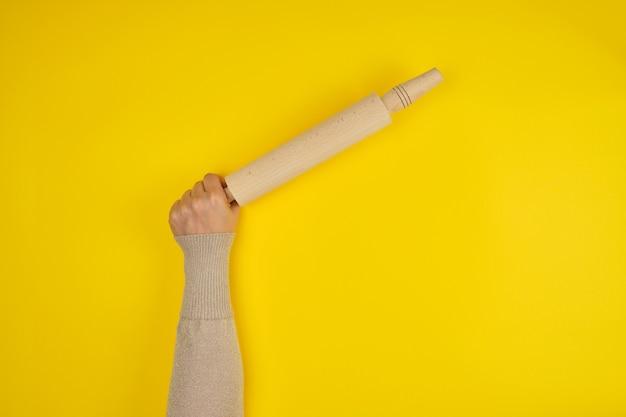 Ręka trzyma drewniany wałek do ciasta