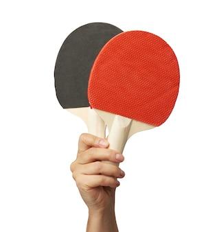 Ręka trzyma dwie drewniane rakiety do tenisa stołowego