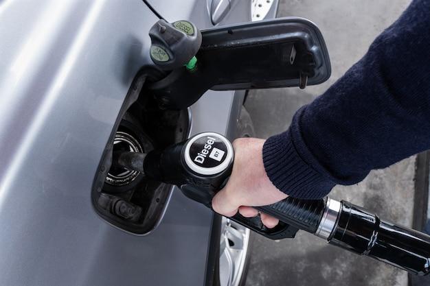 Ręka trzyma dyszę do tankowania samochodów na stacji benzynowej