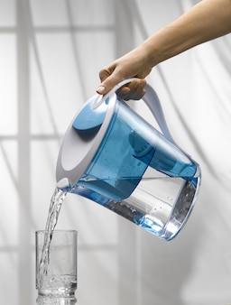 Ręka trzyma dzbanek filtrujący i wlewa trochę wody do szklanki