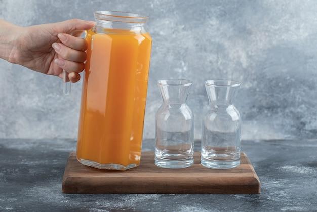 Ręka trzyma dzbanek soku pomarańczowego.