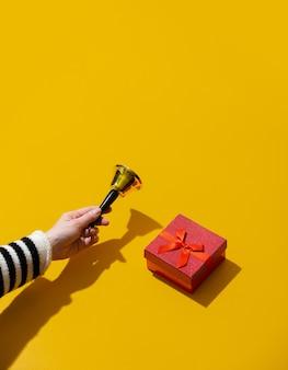 Ręka trzyma dzwonek boże narodzenie w pobliżu pudełka na żółtej powierzchni
