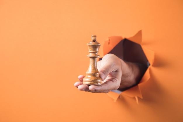 Ręka trzyma figurę szachową na pomarańczowym tle