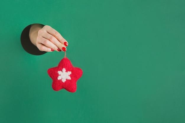 Ręka trzyma filcową czerwoną gwiazdę przez okrągły otwór w zielonym papierze. ręcznie robiona zabawka. świąteczny wystrój.
