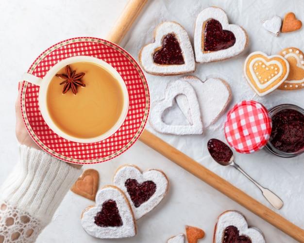 Ręka trzyma filiżankę herbaty o smaku chai, wykonaną przez parzenie czarnej herbaty z aromatycznymi przyprawami i ziołami, nad domowymi ciasteczkami w kształcie serca z dżemem malinowym. koncepcja bożego narodzenia lub walentynki. widok z góry.