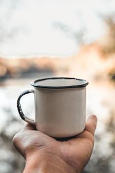 Ręka trzyma filiżankę kawy na naturalnym tle