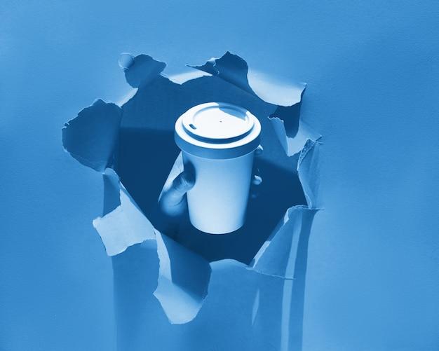 Ręka trzyma filiżankę kawy przez otwór rozdarty w kol
