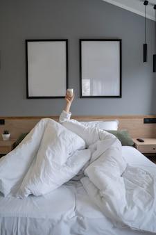 Ręka trzyma filiżankę kawy w domu w łóżku