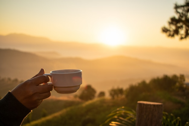Ręka trzyma filiżankę kawy z widokiem na góry i wschód słońca rano