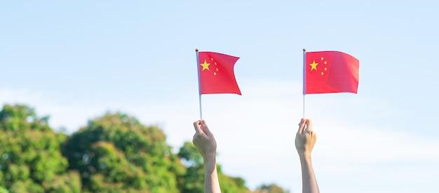 Ręka trzyma flagę chin na tle błękitnego nieba. święto narodowe chińskiej republiki ludowej, dzień świąt państwowych i koncepcje szczęśliwego świętowania
