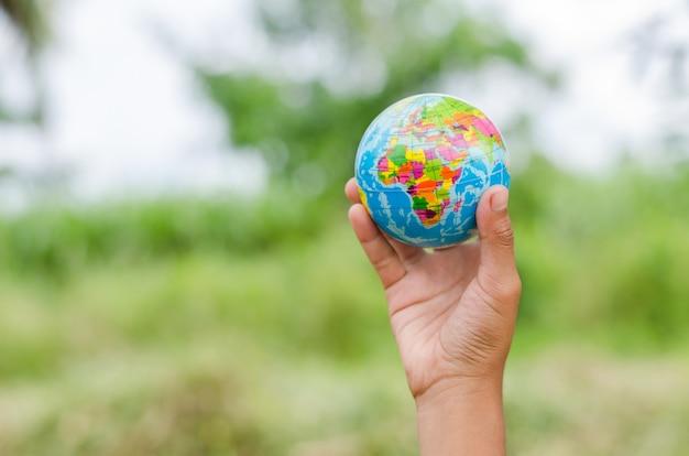 Ręka trzyma globus zabawka. koncepcja uratować ziemię