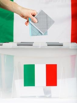 Ręka trzyma głosowanie nad urną wyborczą. w tle włoska flaga. zbliżenie