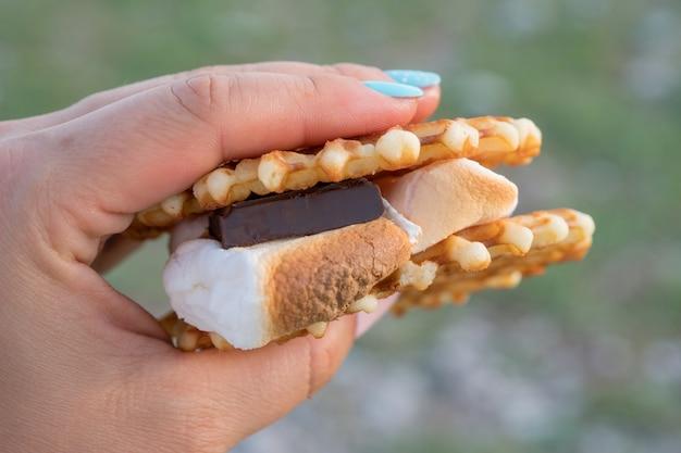 Ręka trzyma gorący smore. słodki deser z ciastek, czekolady i pianki