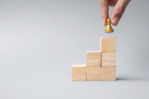 Ręka trzyma górę pionków złote szachy