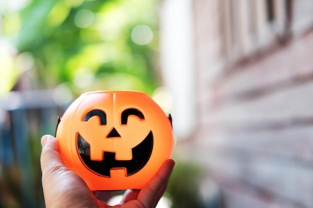 Ręka trzyma halloween bani głowę z złotym światłem w ciemnym nocy bakckground
