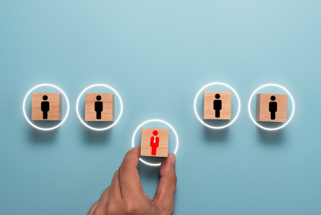 Ręka trzyma i przesuwa czerwoną ikonę menedżera na drewnianym bloku między czarnymi podwładnymi pracownikami. koncepcja rozwoju i promocji człowieka.