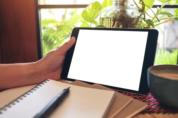 Ręka trzyma i za pomocą czarnego komputera typu tablet z pustym białym ekranem pulpitu z notebookami na stole