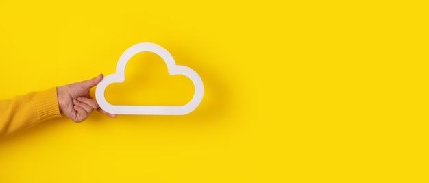 Ręka trzyma ikonę chmury na żółtym tle, makieta panoramiczna