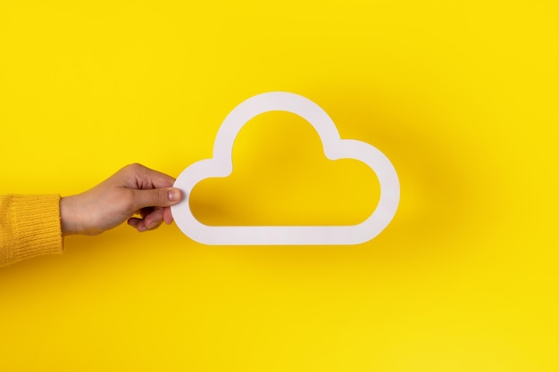 Ręka trzyma ikonę chmury na żółtym tle