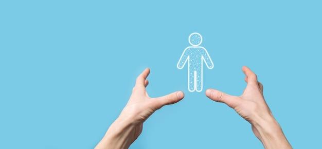 Ręka trzyma ikonę osoby człowieka na ciemnym tle. hr ludzki, ludzie icontechnology process system business z rekrutacją, zatrudnianiem, budowaniem zespołu. koncepcja struktury organizacyjnej.