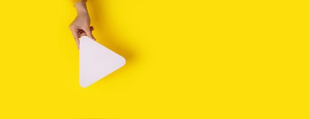Ręka trzyma ikonę przycisku odtwarzacza multimedialnego na modnym żółtym tle, makieta panoramiczna