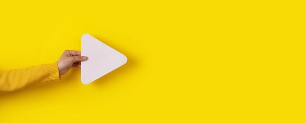 Ręka trzyma ikonę przycisku odtwarzacza multimedialnego na modnym żółtym tle, układ panoramiczny