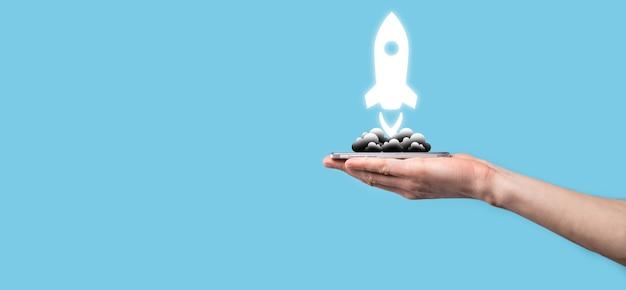 Ręka trzyma ikonę rakiety, która startuje, uruchom na niebieskim tle. rakieta startuje i leci
