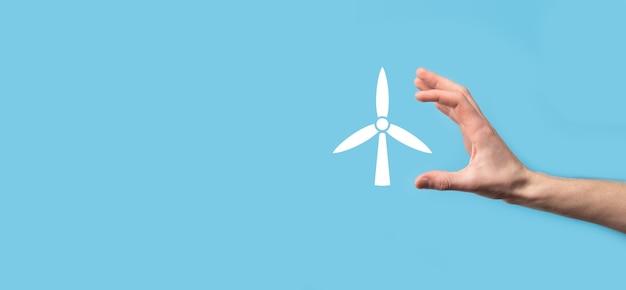 Ręka trzyma ikonę wiatraka, który wytwarza energię środowiska na niebieskim tle.