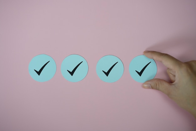 Ręka trzyma ikonę znacznika wyboru papieru wyciąć na różowym tle