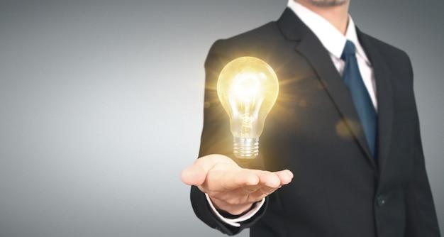 Ręka trzyma iluminującą żarówkę, innowaci inspiraci pojęcie
