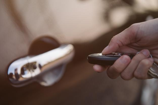 Ręka trzyma inteligentny klucz do blokowania drzwi samochodu