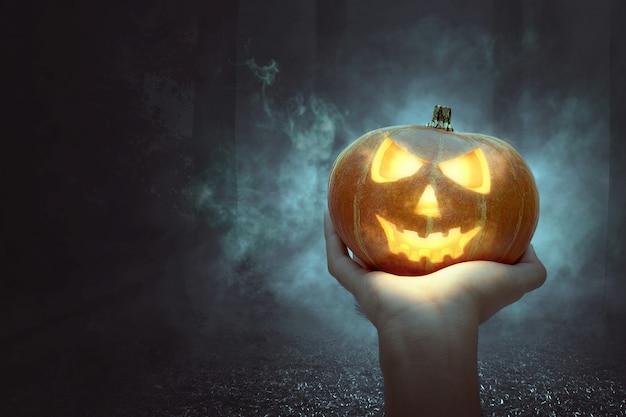 Ręka trzyma jack-o-lantern