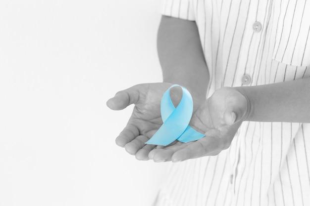Ręka trzyma jasnoniebieską wstążkę na białym tle świadomość raka prostaty