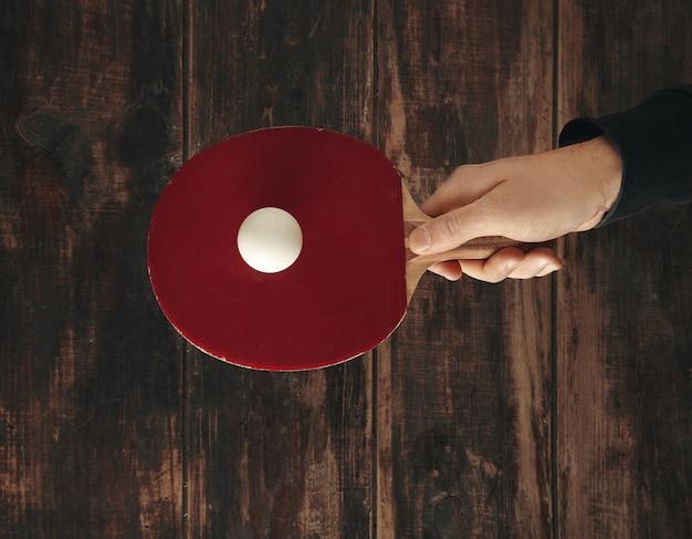 Ręka trzyma jedną profesjonalną rakietę nad drewnianym postarzanym stołem z piłką i jest gotowa do gry w ping ponga