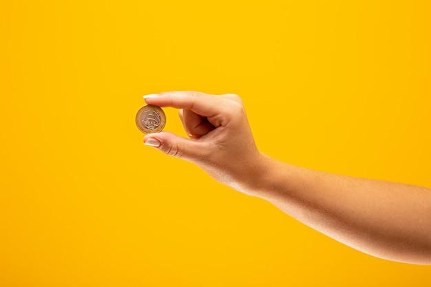 Ręka trzyma jedną real monetę brazylia koncepcji finansowania.