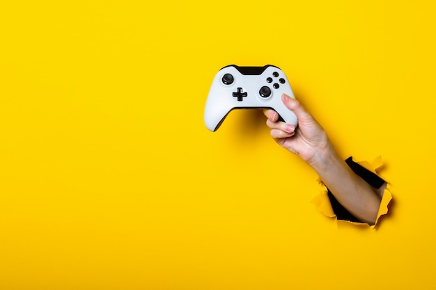 Ręka trzyma joystick na jasnożółtym tle