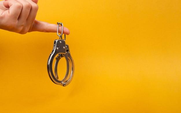 Ręka trzyma kajdanki z miejsca na kopię na żółtym tle, nielegalne aresztowanie.