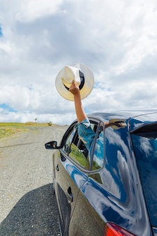 Ręka trzyma kapelusz z okna samochodu